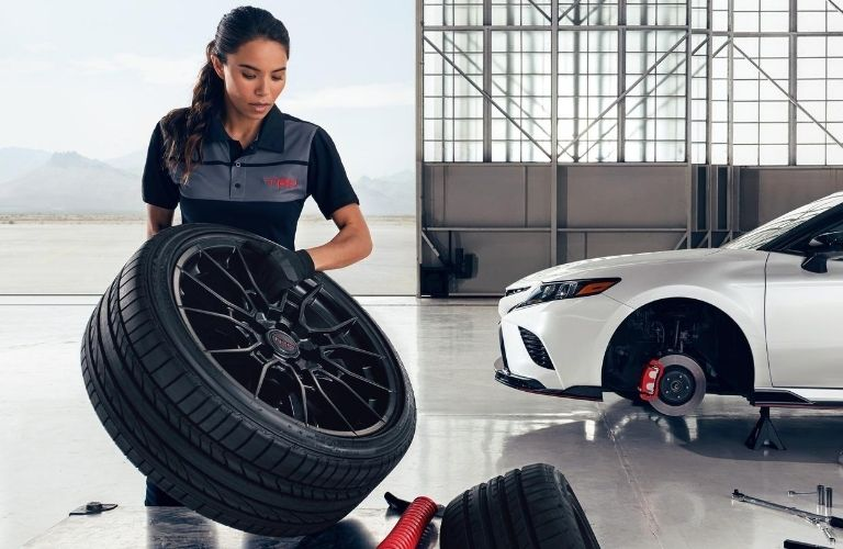 Image of a Toyota technician replacing the tires on a white Toyota vehicle
