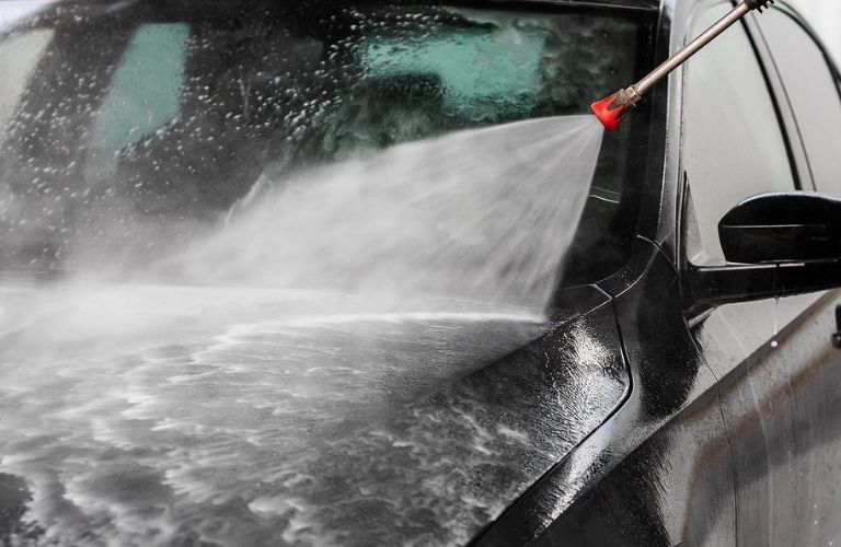 Image of a vehicle's exterior being disinfected and washed