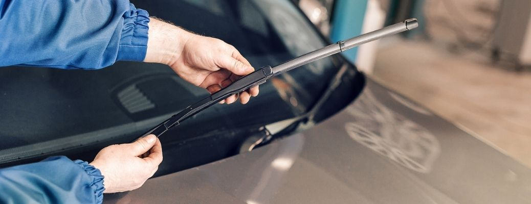Image of a service technician replacing wiper blades on a vehicle