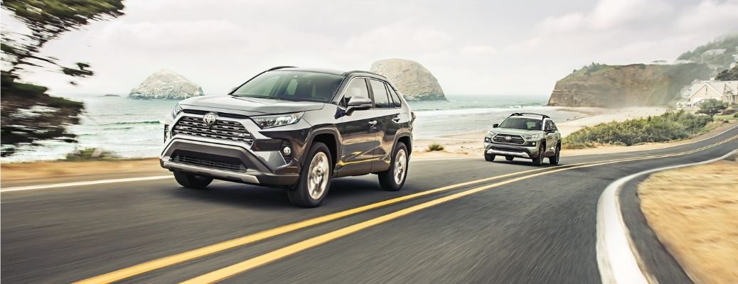 Exterior view of two 2021 Toyota RAV4 models driving down a highway