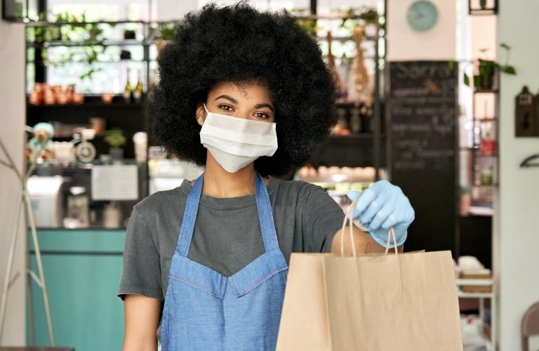 woman at restaurant handing over carryout food bag while wearing a face mask and gloves