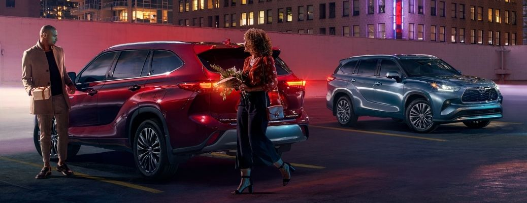 man and woman walking away from parked 2021 Toyota Highlander with another 2021 Toyota Highlander parked nearby at night