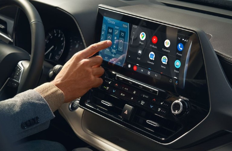 A person reaching over to change a setting on the touchscreen inside a 2021 Toyota Highlander