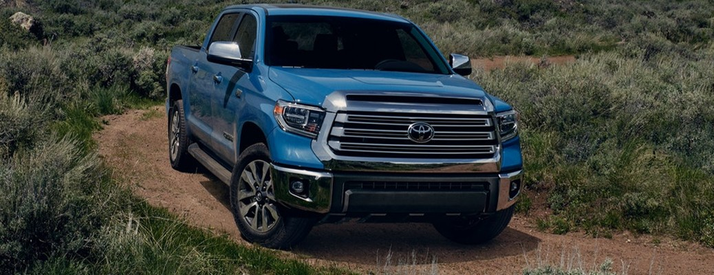 The 2021 Toyota Tundra driving through a dirt path with brush on either side