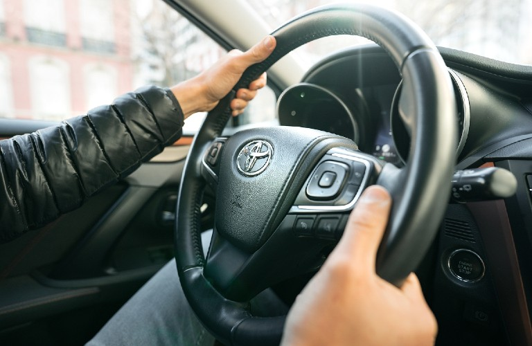 Two hands on a Toyota vehicle steering wheel