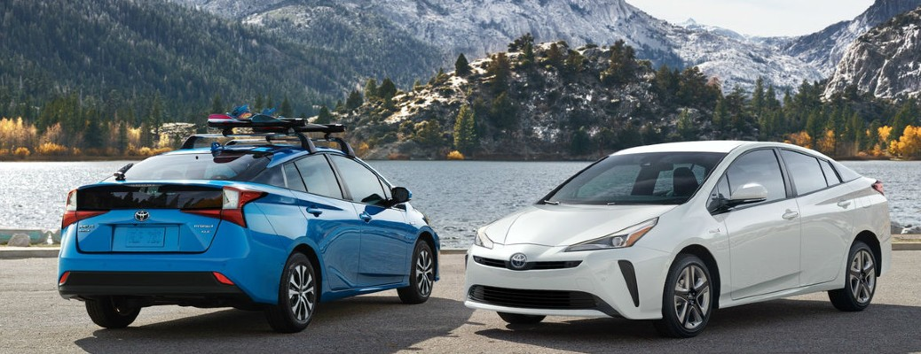 Two 2021 Toyota Prius vehicles parked near water and mountains