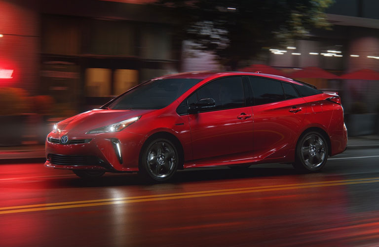 A red-colored 2021 Toyota Prius driving on a road