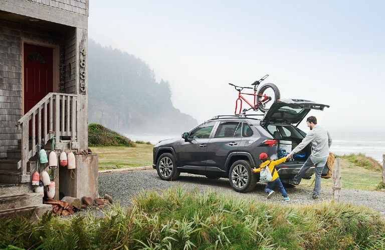 A 2021 Toyota RAV4 packed with cargo items with a family nearby