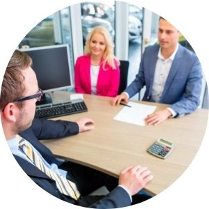 Car Salesman with Man and Woman at a Desk