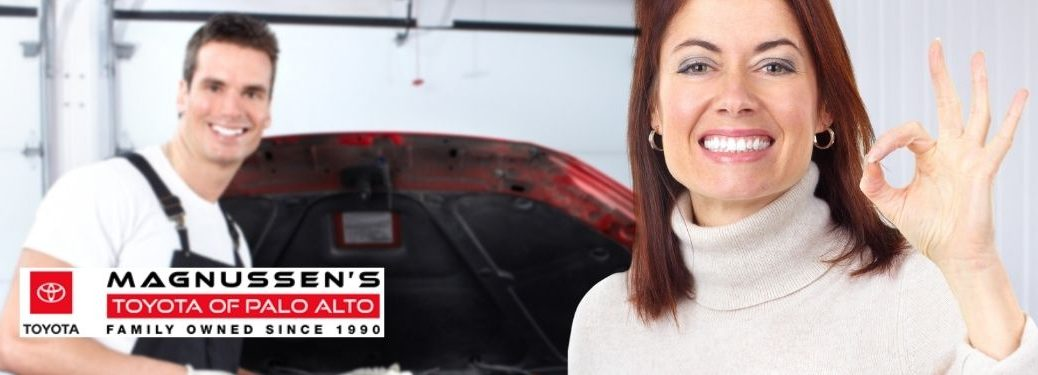 Happy Woman Giving OK Symbol and Mechanic in a Garage with Toyota of Palo Alto Logo