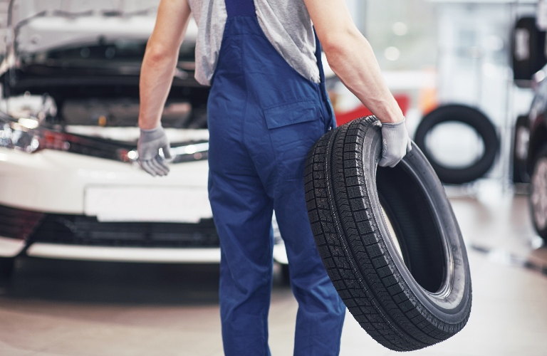 Mechanic walking with a tire in one hand