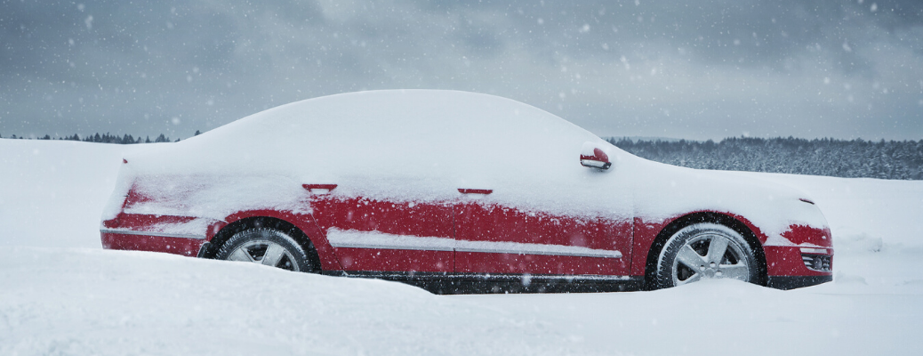 Red car stranded in packed snow