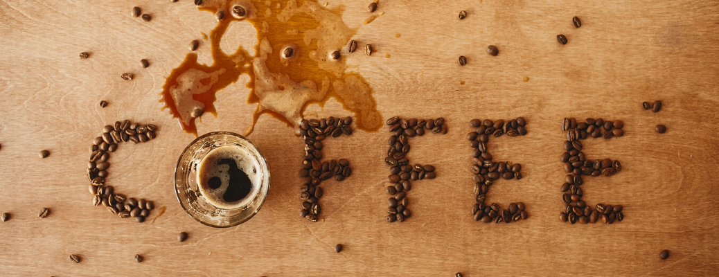 Coffee word made of roasted coffee beans and spilled espresso from cup on wooden table