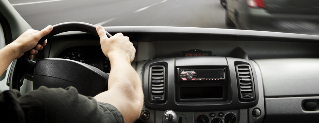 Male driver's hands on the steering wheel of vehicle
