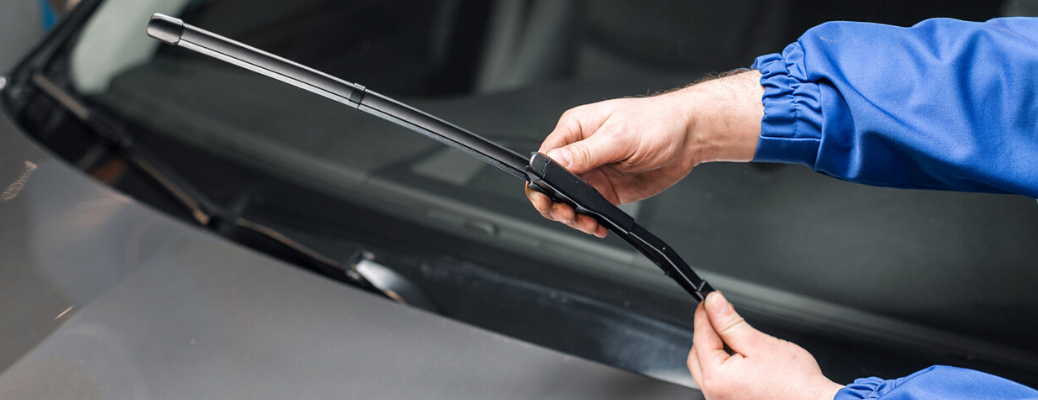Closeup of hands replacing wiper blades of a vehicle