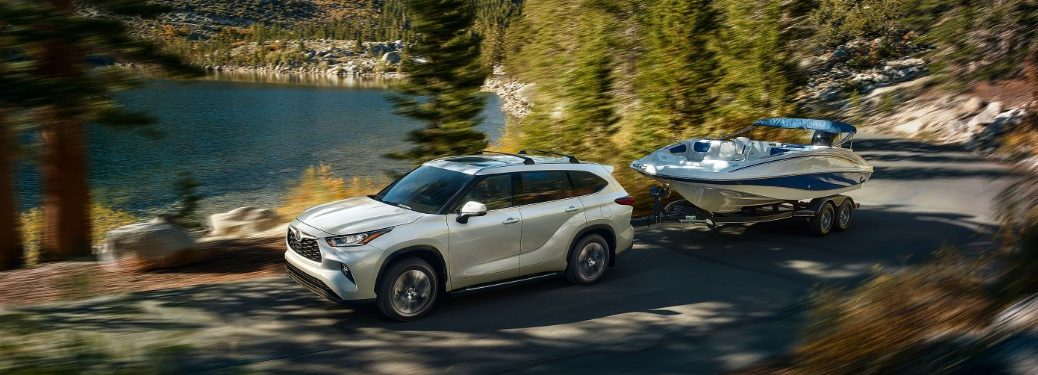 white 2020 Toyota Highlander towing a boat