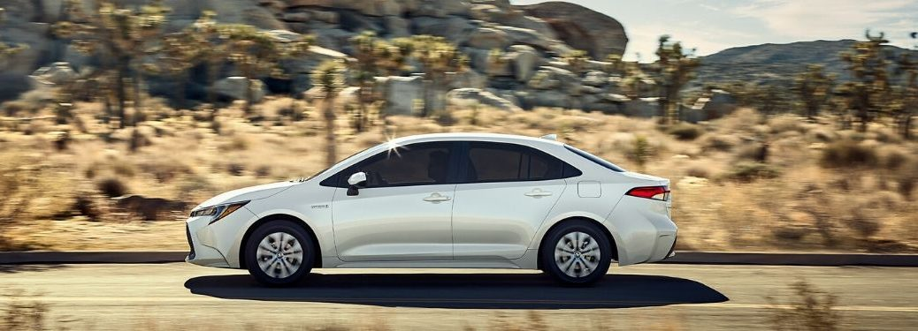 White 2020 Toyota Corolla driving down road with rocks and dessert in background