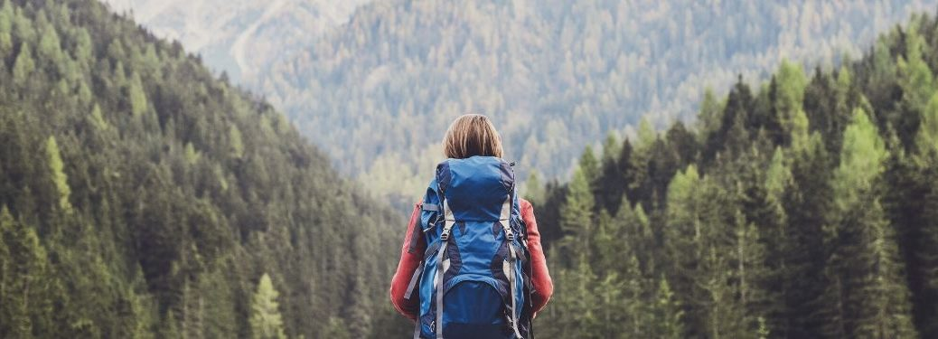 Girl wearing backpack standing in front of tree covered mountains