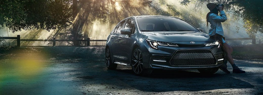 2020 Toyota Corolla dark grey paint with woman leaning on hood