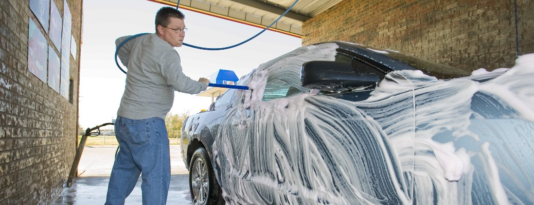 person washing soapy car with water hose