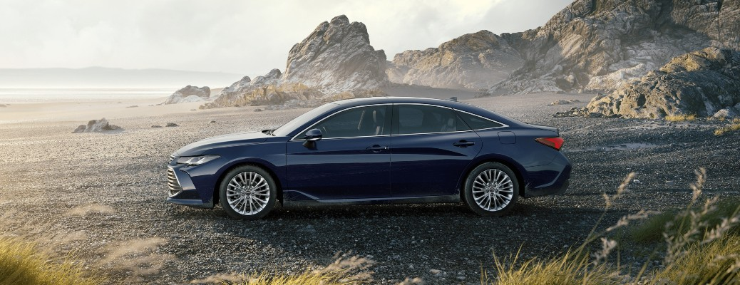 2021 Toyota Avalon blueprint parked on rocky shore with grass in foreground