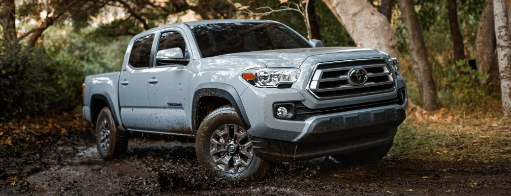 2021 Toyota Tacoma white driving through muddy forest trail