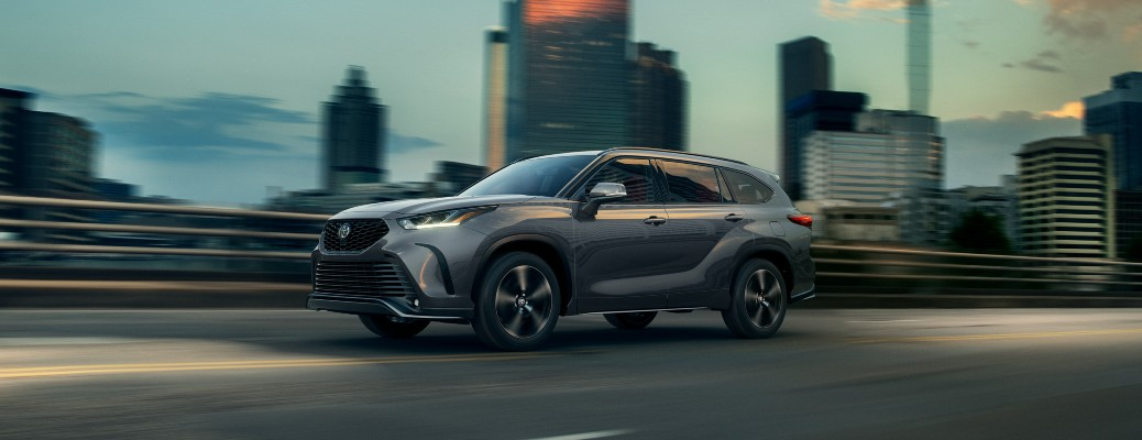 2021 Toyota Highlander gray driving on bridge at twilight