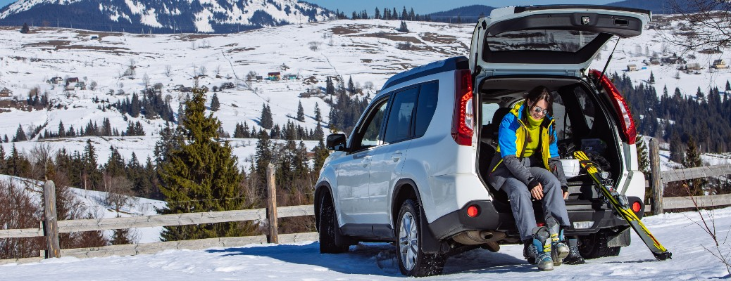 woman sitting in the back of SUV with ski equipment
