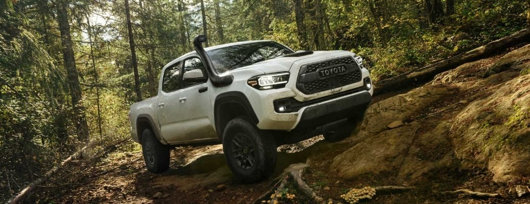 2020 Toyota Tacoma TRD Pro driving over rocks in a forest