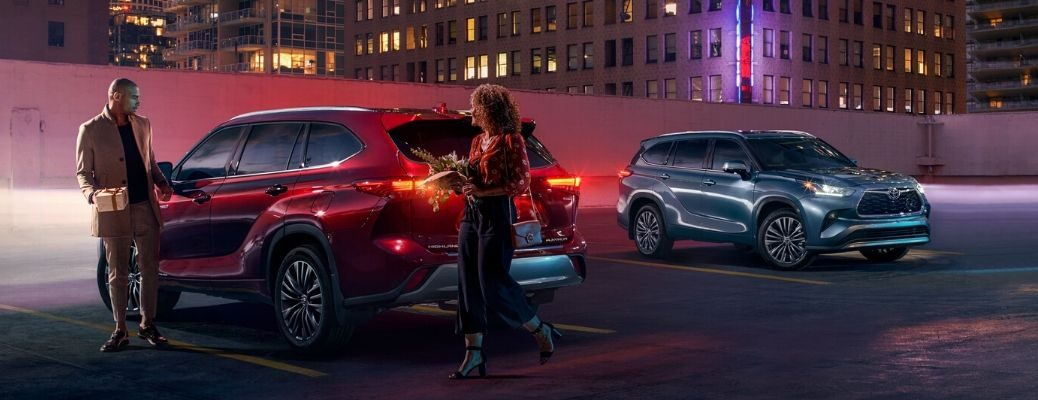 man and woman in parking lot with two 2020 Toyota Highlander models at night
