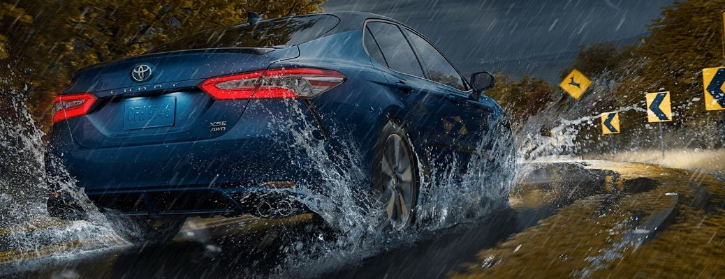 rear view of 2020 Toyota Camry rounding a curve during a thunderstorm