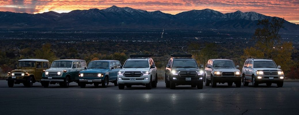 Toyota Land Cruiser models in a row with a mountain in the background