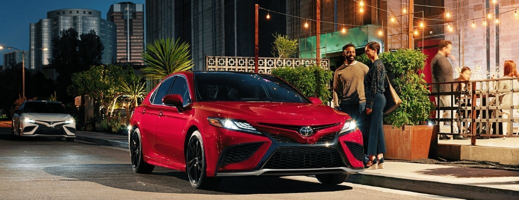 a couple approaching a parked 2021 Toyota Camry