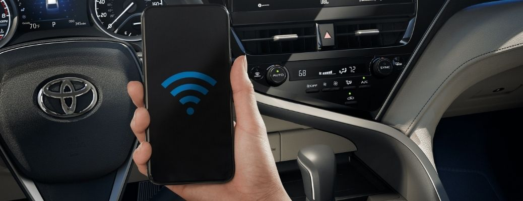 hand holding a phone with wifi icon on it inside a 2021 Toyota Camry