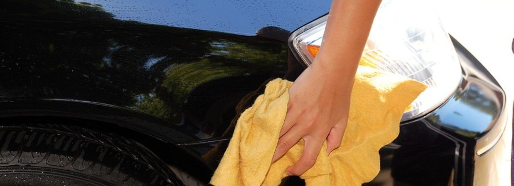 person using a yellow rag to clean their vehicle