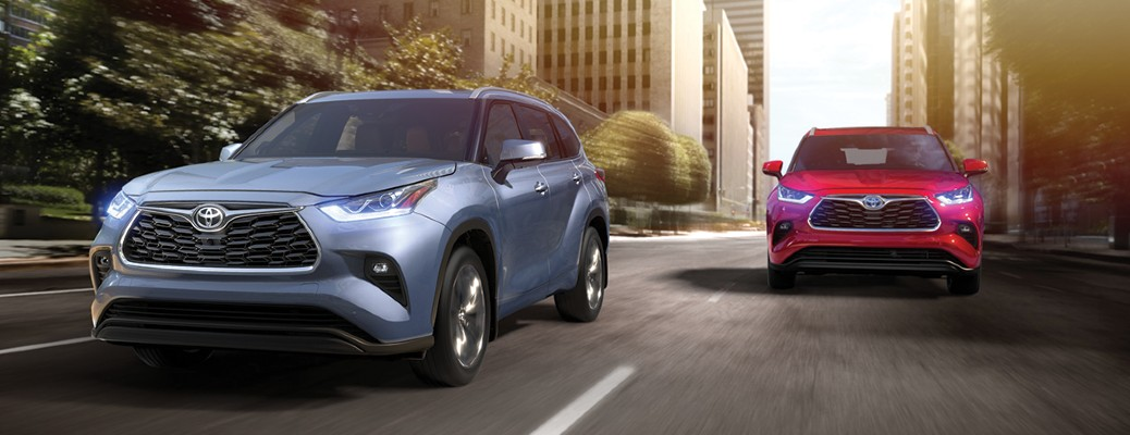 The front image of a blue and red 2020 Toyota Highlander driving down a city road.