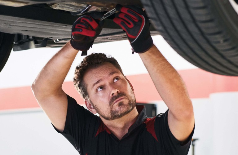 A Toyota technician working on a vehicle at a local service department.