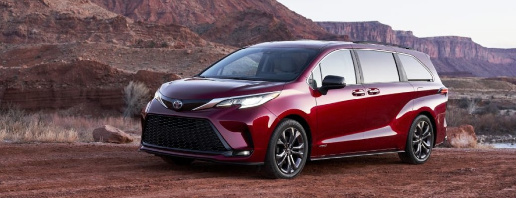 A front and side view of a dark red 2021 Toyota Sienna parked in a rocky canyon.