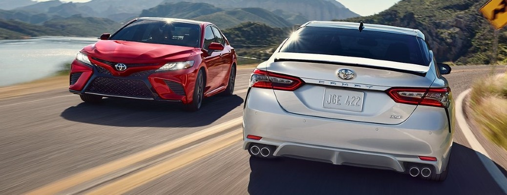 A red and a white 2020 Toyota Camry passing each other on a hilly road.