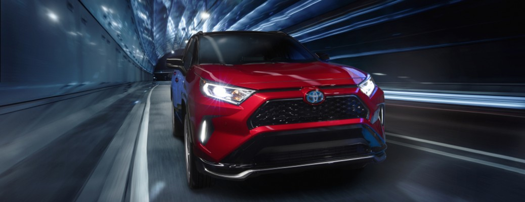 The front image of a red 2021 Toyota RAV4 Prime driving quickly through a tunnel.