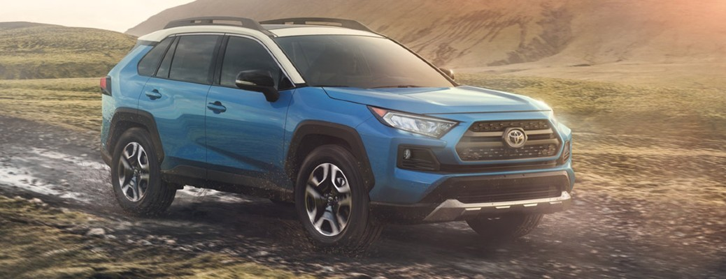 A blue 2020 Toyota RAV4 driving on an off-road path.