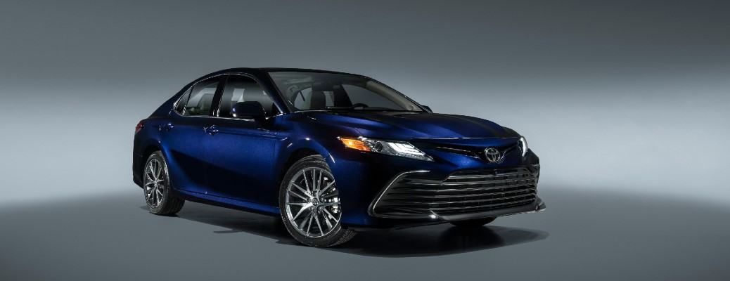 The front and side view of a blue 2021 Toyota Camry.