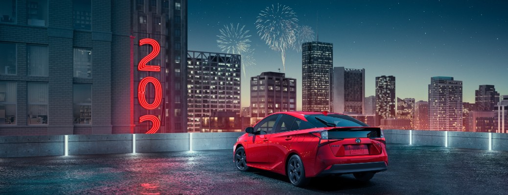 A red 2021 Toyota Prius 20th Anniversary Special Edition parked along a city skyline.