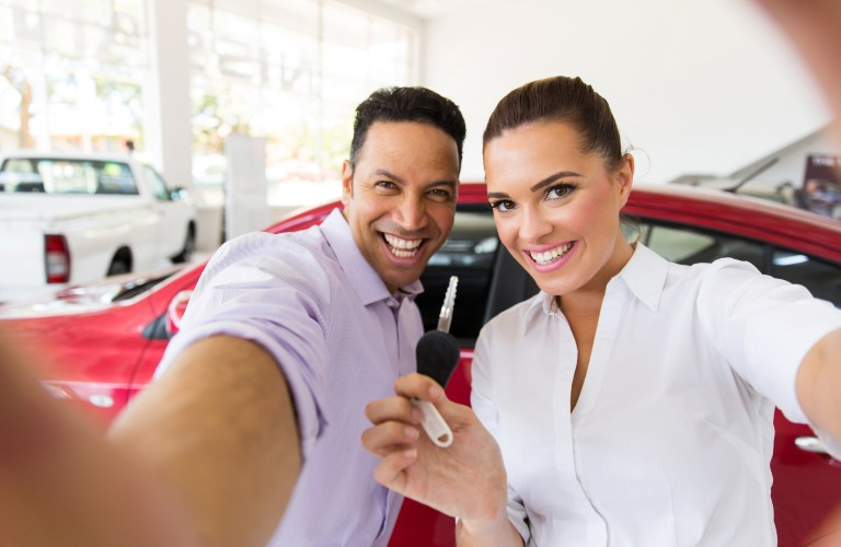 A young couple taking a selfie in front of a new red car.