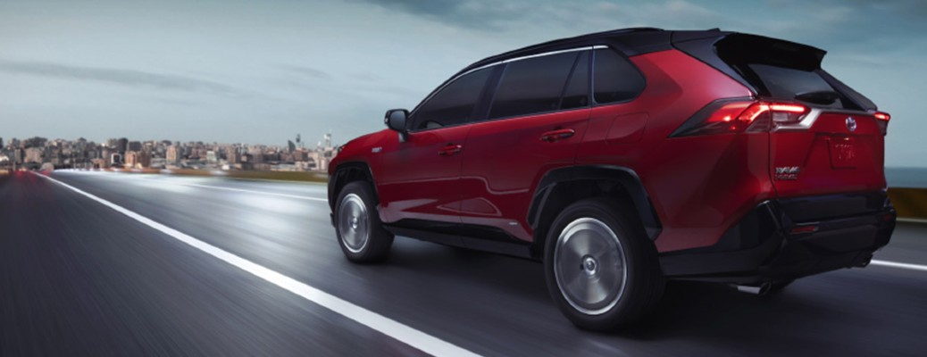 The side and rear view of a red 2021 Toyota RAV4 Prime driving towards a city.