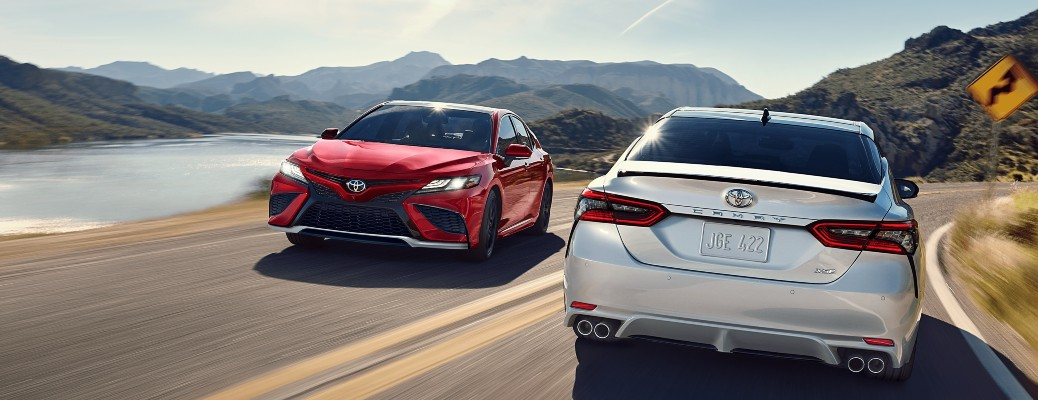 A red 2021 Toyota Camry driving past a white 2021 Toyota Camry.