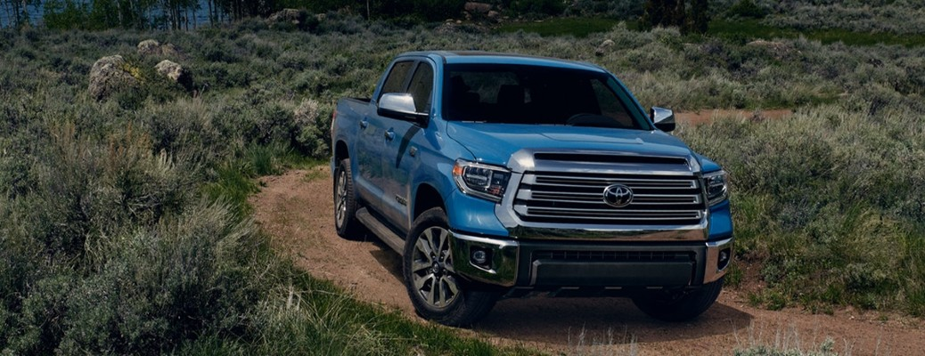 The front view of a blue 2021 Toyota Tundra driving on a trail.