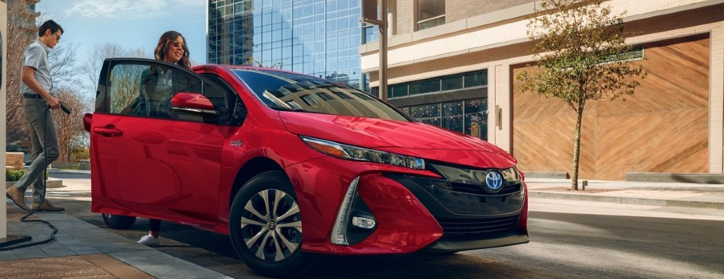 A young man placing a plug-in cord into a red 2021 Toyota Prius Prime while a woman gets into the passenger seat.