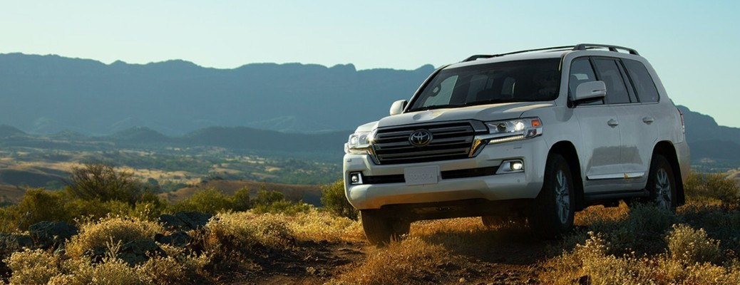The front view of a white 2021 Toyota Land Cruiser driving off-road.