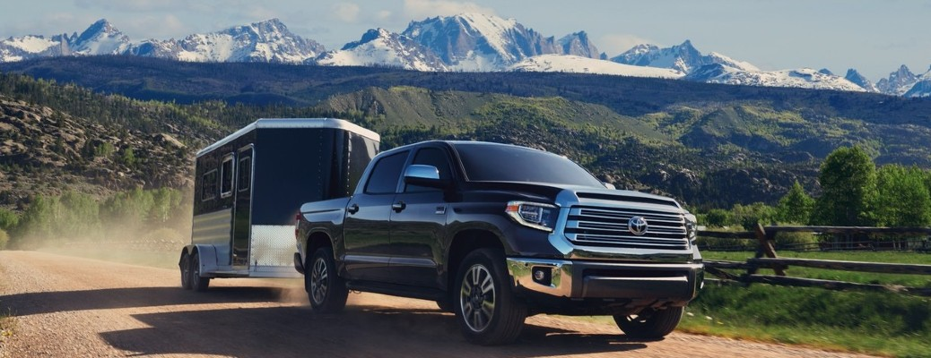 The front and side view of a black 2021 Toyota Tundra hauling a trailer away from mountains.
